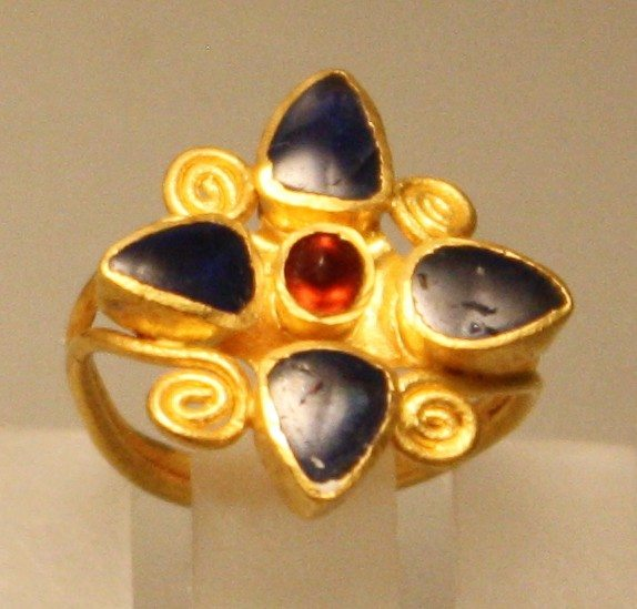 Roman gold and saphire ring, second half of the 2nd century CE. The ring has a garnet centre stone. From an unidentified marble sarcophagus in Rome. Palazzo Massimo, Rome.