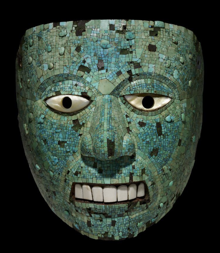 A turquoise mosaic mask representing Xiuhtecuhtli, the Aztec god of fire, 1400-1521 CE. The mask is of cedar wood with mother-of-pearl eyes, conch shell teeth and once with gold leaf on the eyelids. (The British Museum, London).