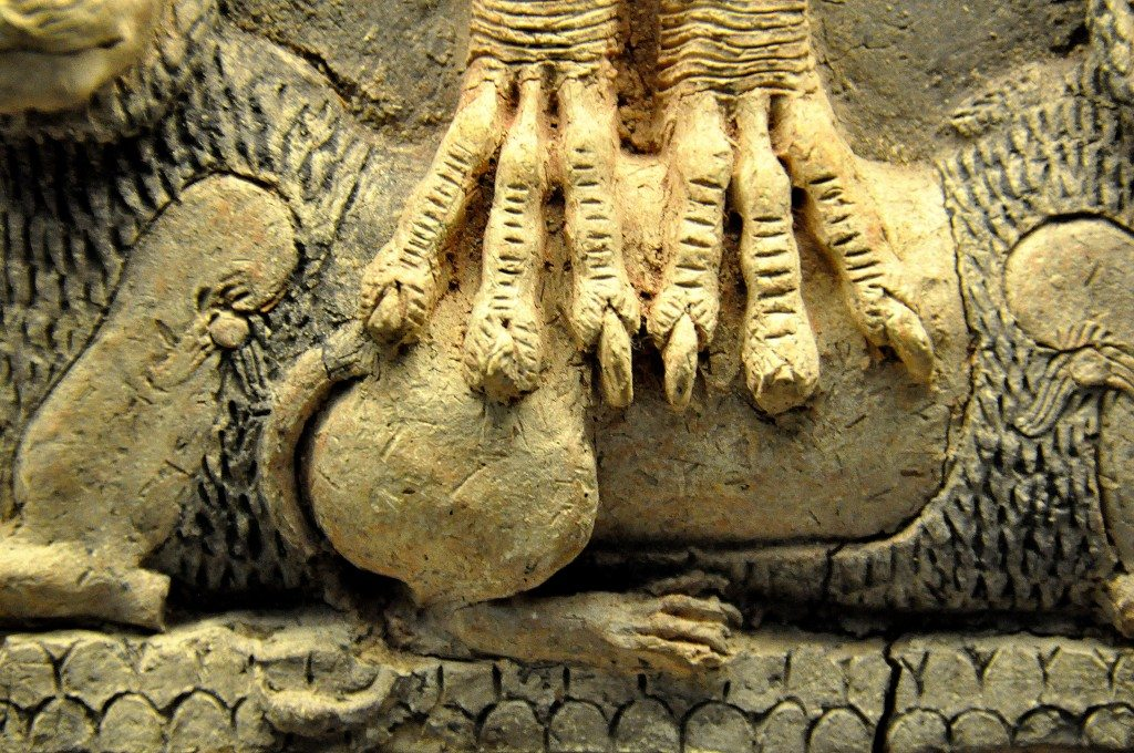 The deity's feet are of a bird. Note the scutes and the talons.
