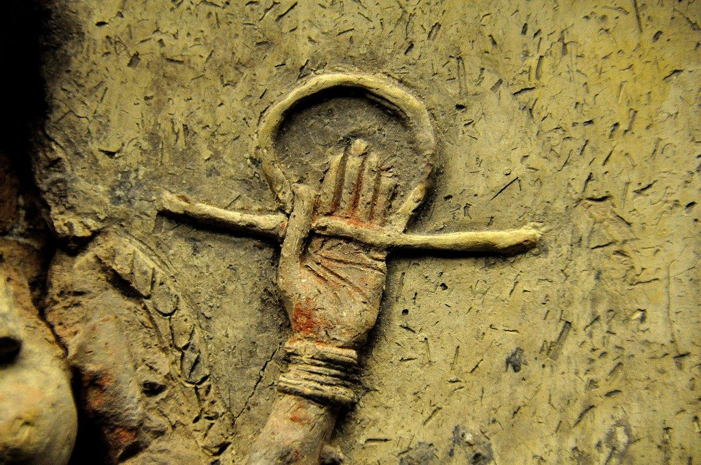 A close-up image of the left arm. The palm faces the viewer. The fingers are extended and adducted while the thumb is flexed and adducted. The hand holds the rod-and-ring symbol of divinity. Traces of red color are still seen. Note the wrist bracelet and the palm creases.