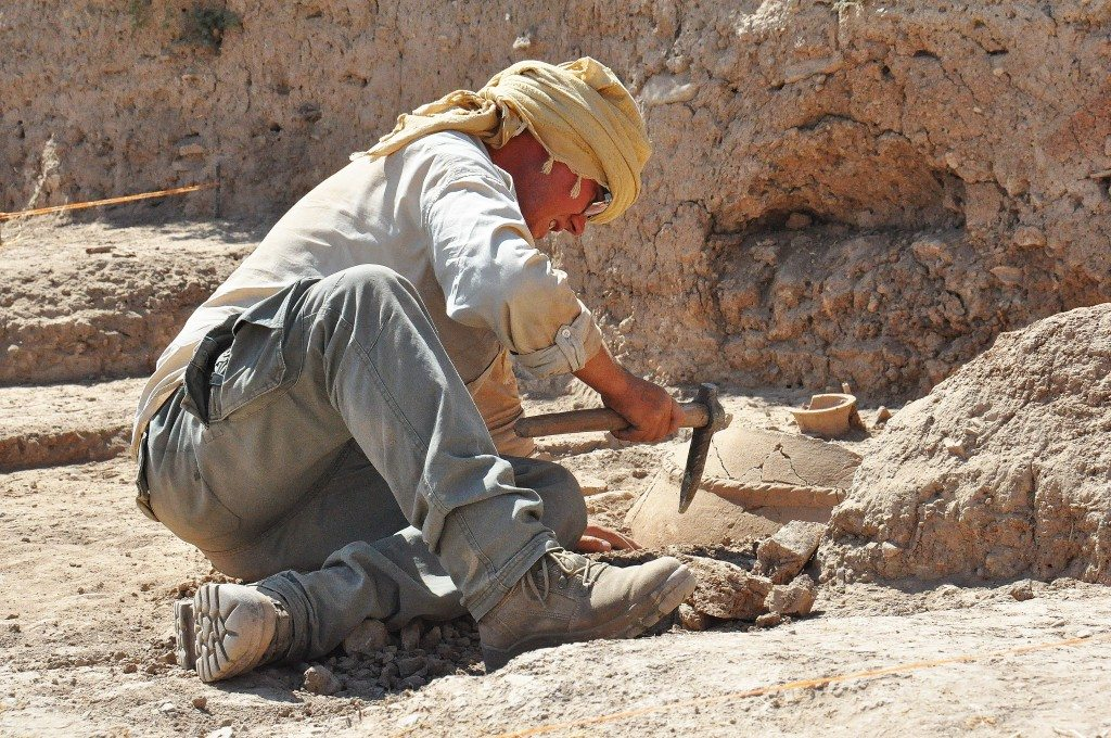 An archeologist tries to uncover a large pottery jar.