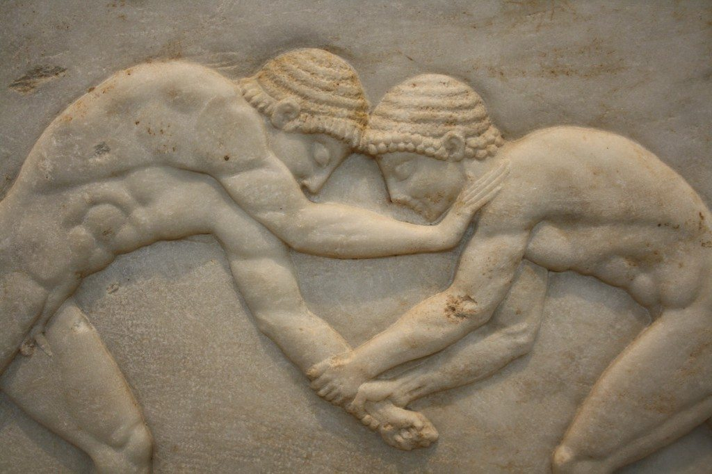 A detail of a marble funerary kouros base showing two wrestlers, 510-500 BCE.