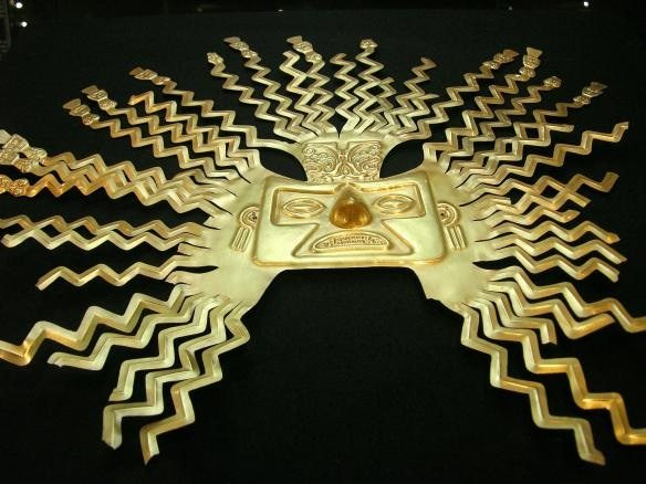 A gold-sheet mask representing the sun god Inti from the La Tolita part of the Inca empire. The design is typical of masks of Inti with zig-zag rays bursting from the head and ending in human faces or figures. (National Museum, Quito, Ecuador).