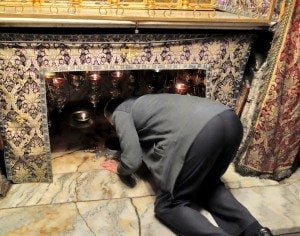 A Christian worshiper kneels at the spot in Bethlehem where Jesus is believed to have been born. (photo: Rick Steves)