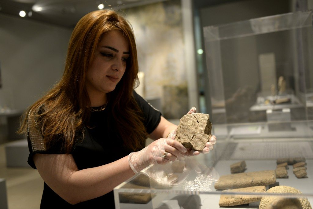 Miss Hazha Jalal, manager of the tablet's section of the Sulaymaniyah Museum, holds the tablet. The Sulaymaniyah Museum, Iraq. ©Osama S. M. Amin.