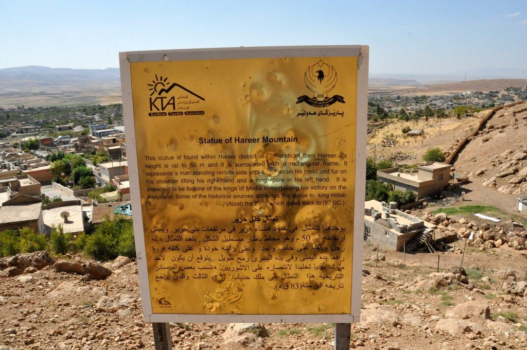 "This sign mentions ""Kurdistan Tourism Association and The Governorate of Hawler."" It describes the relief in 3 different languages. The sign lies at the foot of the mountain. Note the village on the background. ©Osama S. M. Amin."