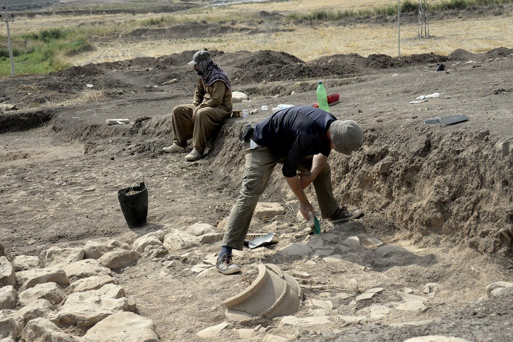 One of the French archaeological team excavates pottery fragments; part of a large pottery pot can be seen. Photo © Osama S. M. Amin.