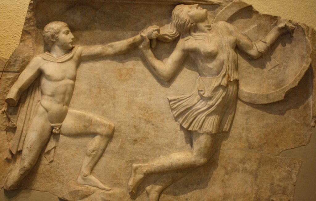 A plaque relief depicting a Greek pursuing an Amazon. Part of a pair of duplicate relief slabs. 2nd century CE Roman copies of scenes from the shield of Athena on the Athena Parthenos statue by Pheidias in the Parthenon.