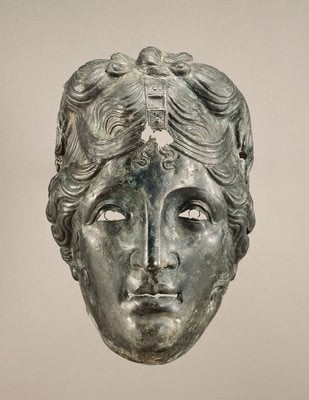 Mask from a Cavalry Helmet from Asia Minor, 75–125 CE. The J. Paul Getty Museum (72.AB.105). This mask was worn by a male soldier, but a Roman man would not have worn such long, carefully curled hair with a center part. The top-knot indicates it might represent Apollo, or possibly a female goddess like Aphrodite or Artemis. Because of the delicately outlined eyes and hairband, which originally included other materials such as gold, silver, or jewels, this was probably not worn in combat, but in a tournament or parade. We don't know why the mask is shown with this hairstyle; it may relate to the military unit's patron god or goddess, whose protection is invoked. Masks like this may also have been worn by soldiers in contests that re-enacted scenes of Greek myth and history.