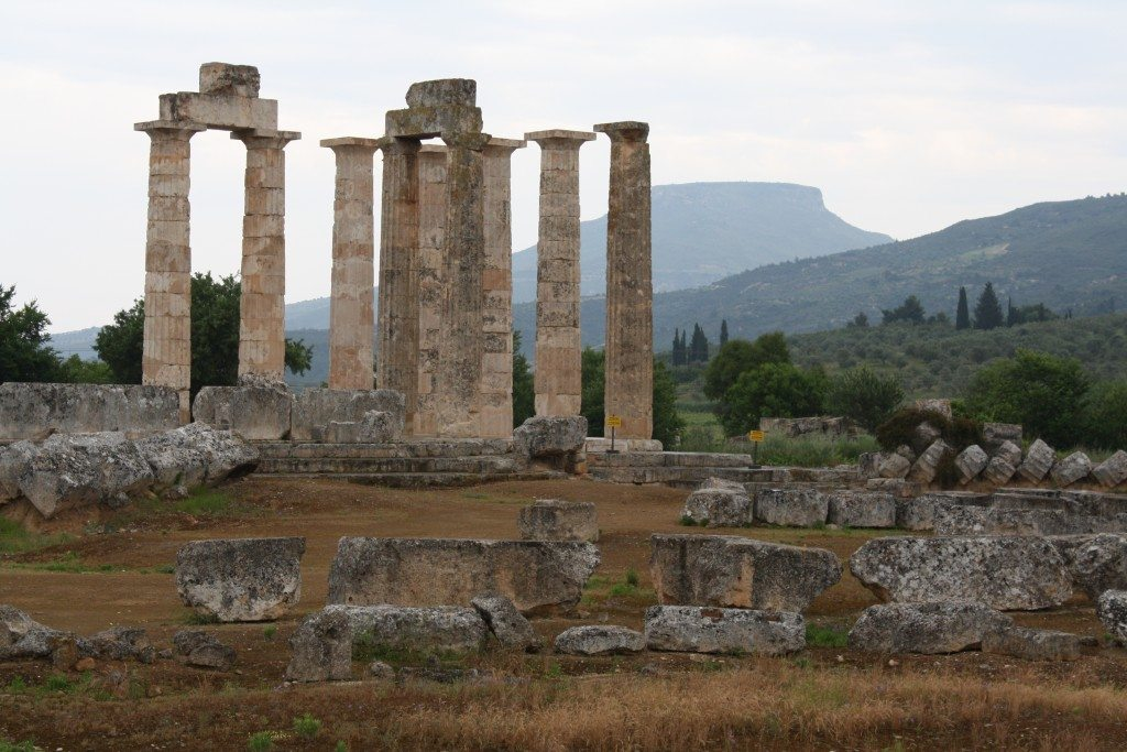 The temple of Zeus at Nemea was constructed in c. 330 BCE and replaced an earlier temple which had stood from the 6th to 5th century BCE. Inside was a cult statue of the god. The temple was composed of an exterior Doric peristyle (6x12 unusually tall and slim columns) with an interior Corinthian colonade, topped by a second story of the Ionic order. There were no sculpted decorations on the exterior. It is regarded as the last of the great Doric temples of the Classical tradition. The temple measures a little over 20x42m, the material used is locally quaried limestone. Three of the now standing columns have stood since original construction (slighty darker colour), the others have been repositioned in the early 2000's CE using the orginal, fallen drums. Photo © Mark Cartwright.