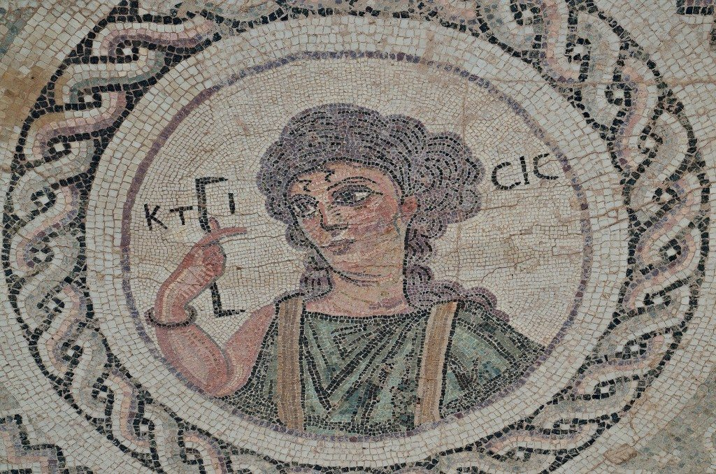 Byzantine mosaic emblema in the House of Eustolios depicting a young woman in a medallion holding a measuring instrument equating of a Roman foot, the Greek inscription identifies her as Ktisis, the personification of Creation, Kourion