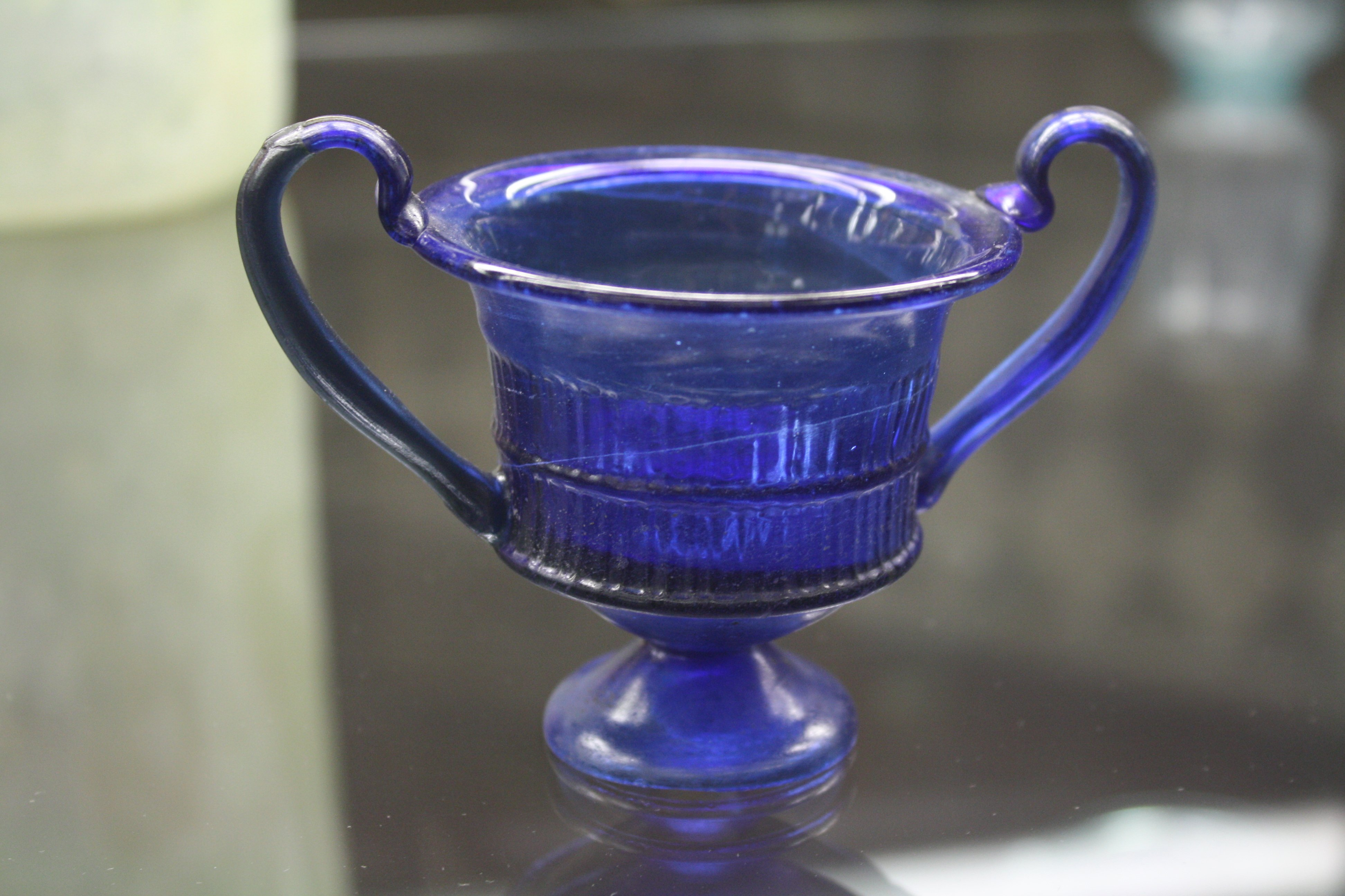 A glass kantharos or drinking cup.