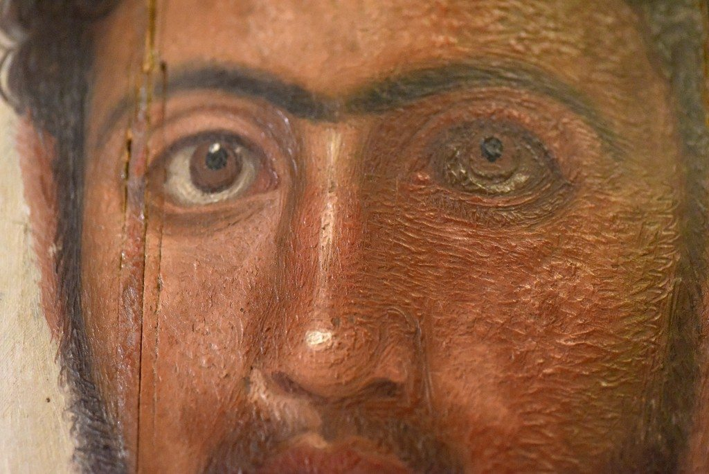 "Detail of a mummy portrait from Hawara. This is a thin lime (Tilia species) wooden panel with encaustic wax mummy portrait. of Petrie's ""red youth"". The man has curly light beard and moustache. It appears that a sharp tool was used to delineate the shape of the face, ears, and eyebrows. From Hawara cemetery, Egypt. 1st to 2nd centuries CE. The Petrie Museum of Egyptian Archaeology, London (with thanks to The Petrie Museum of Egyptian Archaeology, UCL). The Petrie Museum has the largest collection of these ""portraits"" outside of Egypt. Originally, these portraits were placed over their mummified body; these images were hailed as the 1st life-like representations of real people on their 1st exhibition in London in 1888 CE. These portraits were excavated in 1888-1889 CE and 1901-1911 CE."