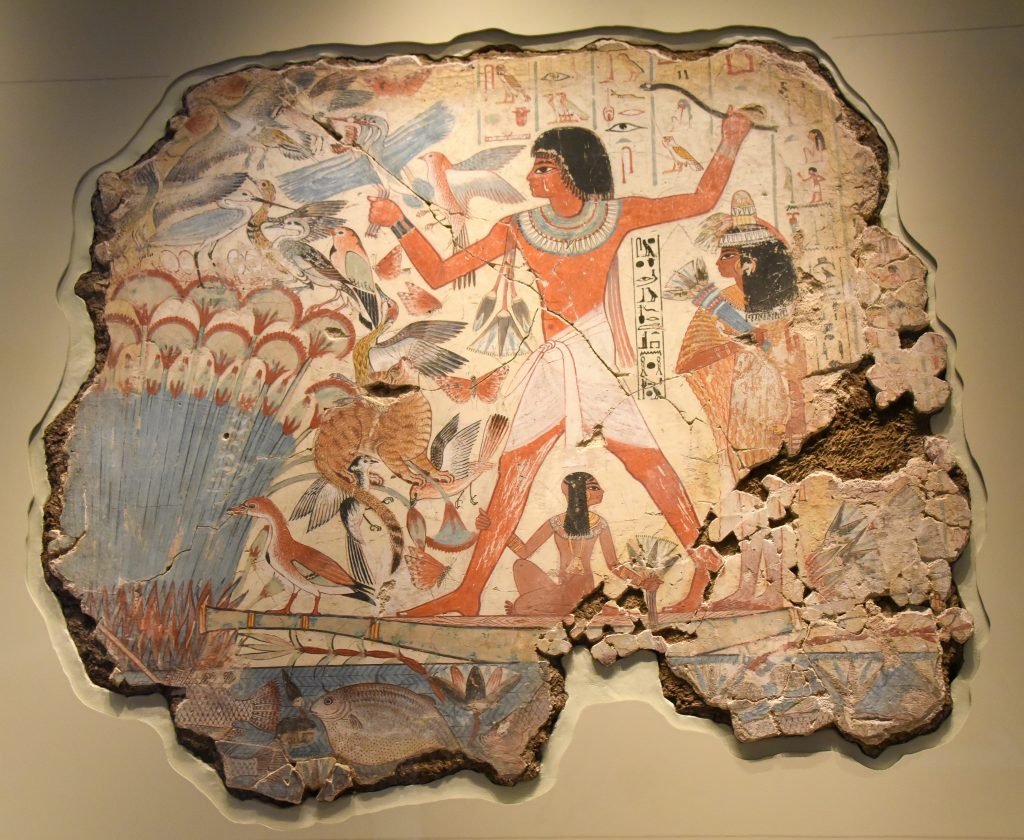 "Nebamun is in a small boat, hunting birds with his wife, Hatshepsut and their young daughter in the marshes of the Nile. Scenes of leisure had already been a traditional parts of tomb-chapel decorations for centuries and they show the tomb's owner ""enjoying himself and seeing beauty"" in the afterlife, as the hieroglyphic caption here says. Fertile marshes were the place of rebirth and eroticisim, making this more than a simple image of recreation. The huge striding figure of Nebamun dominates, forever happy and forever young, surrounded by the rich and teeming life of the marsh. Hunting not only supplied food, but represented Nebamun's triumph over the forces of the chaos. The British Museum, London. Photo © Osama S. M. Amin."