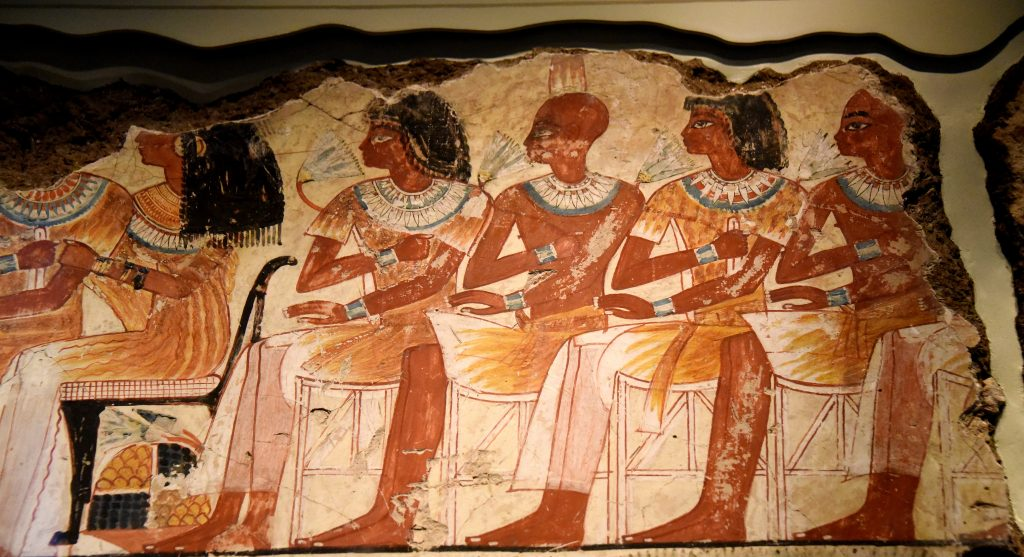 The young men sit on rows of stools, beside a group of young women who sit on chairs with cushions. Men and women skin are painted in different colors; the men are tanned while the women are paler. In one place, the artists altered the drawing of these wooden stools and corrected their first skete with white paint. The Brtiish Museum, London. Photo © Osama S. M. Amin. Nebamun tomb-chapel.