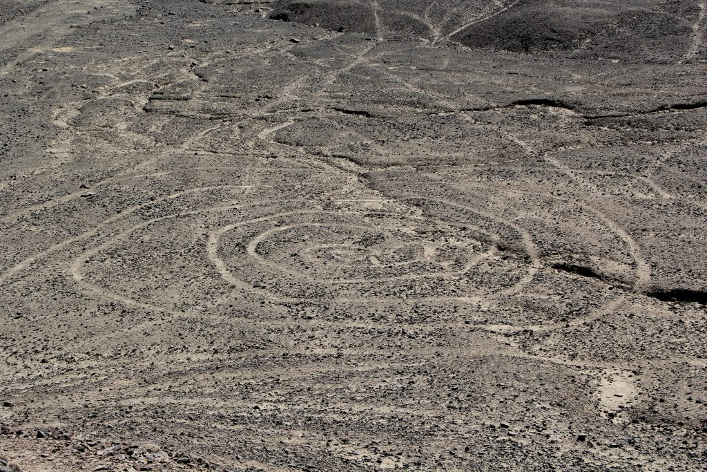 The spiral begins in at a central point and infinitely winds outwards into eternity. Image © Caroline Cervera. Nazca lines
