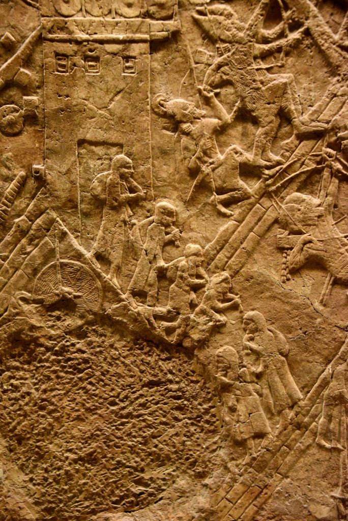 The Lachish defense forces had started to collapse. The city gate has been opened and the city's people are fleeing Lachish, holding belongings, whatever they could bring with them. This detail shows women and one man; they are walking down the hill and have reached the Assyrian artificial ramp. It seems that the Assyrian army let them go, without killing them on the spot. The surrounding battle field is like hell; the Assyrian continue to progress successffully while the defenders of Lachish are desperately resisting the overwhelming invasion. From Nineveh (modern-day Mosul Governorate, Iraq), Room XXXVI of the South-West Palace, panels 7. The British Museum, London. Photo © Osama S. M. Amin.