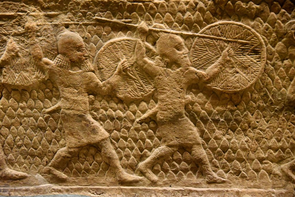 The beginning of the attack on Lachish in 701 BCE. This is a detail of a large stone wall panel which shows Assyrian soldiers in action, holding their long spears and rounded shields. From Nineveh (modern-day Mosul Governorate, Iraq), Room XXXVI of the South-West Palace, panels 5-6. The British Museum, London. Photo © Osama S. M. Amin.