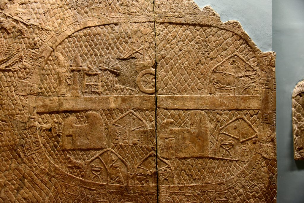 This panel shows the Assyrian base camp, from which the siege was conducted. It is fortified, with a road through the middle. Servants are work in tents, and 2 priests are performing a ceremony in front of the chariots on which are mounted the standards of the gods. Photo © Osama S. M. Amin.