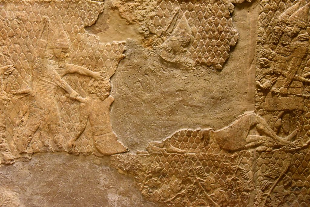 "Some of the prisoners are being ""beheaded"". The one on the left is about to get his through cut by an Assyrian soldier. Another one on the right (most of his body was lost) was already beheaded and dead; his supine and flaccid posture suggest that. The Assyrian literature clearly mentioned that only the heads of a rebellion or enemy (king, prince, commander-in-chief, high ranking officials,...etc.) face execution, usually through beheading. From Nineveh (modern-day Mosul Governorate, Iraq), Room XXXVI of the South-West Palace, panels 11-13. The British Museum, London. Photo © Osama S. M. Amin."