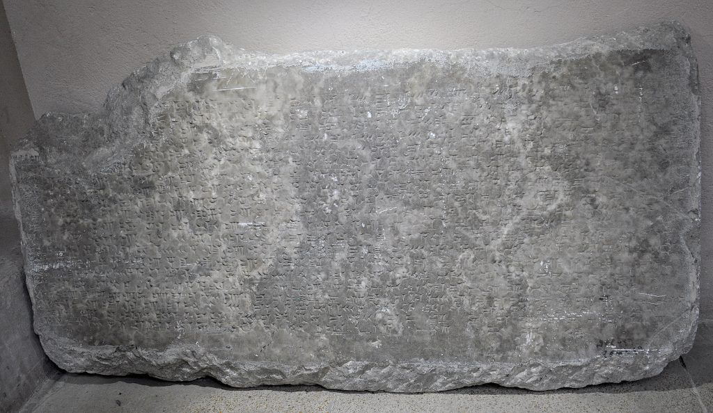 """This fragment does not depict any scene or figure. The """"Standard Inscription' of Ashurnasirpal II is the only content, filling out all of the surface of relief's fragment. The cuneiform inscriptions are clear. Note the label at the right lower angel. it reads in Arabic language """"م م ق 46""""; this is translated to Mosul Museum 46. The other label below it is worn out. Not on display. Exclusive photo; never-before-published. The Sulaymaniyah Museum, Iraqi Kurdistan. Photo © Osama S. M. Amin."""