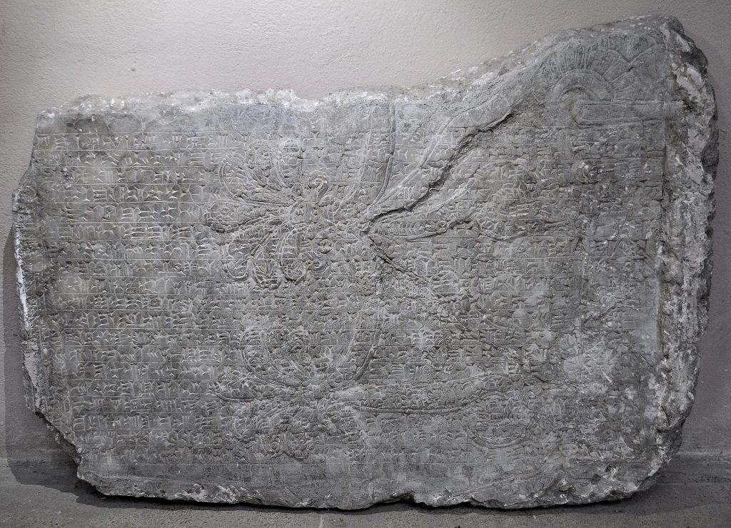 """Fragment of a wall relief from the North-West Palace of Ashurnasirpal II at Nimrud. The """"Standar Inscription"""" of Ashurnasirpal II runs over the left half of a sacred tree or tree of life. The right part of the upper margin was cut out in a way to preserve part of the sacred tree; therefore that margin appears non-horizontal. Not on display. Exclusive photo; never-before-published. The Sulaymaniyah Museum, Iraqi Kurdistan. Photo © Osama S. M. Amin."""