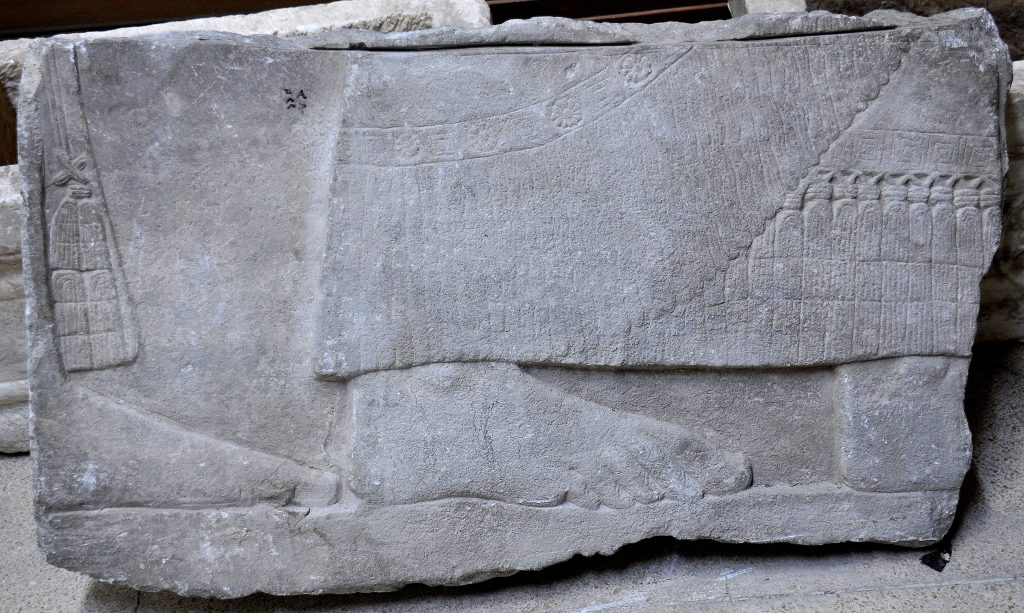 "This fragment was labeled, at the left upper part, using Arabic language, ""م م ق 380"" which means Mosul Museum 380. Note the ""horizontal slit"" at the upper margin, which seems to be caused by electric saw, during the cutting process of the relief. The relief shows part of the lower legs of 2 men, bare-footed. They wear long firnged robe, exquisitely carved. It is unknown whether this fragment came from the North-West Palace or from another palace within Nimrud, or from other Assyrian palaces in Nineveh or Dur-Sharrukin. Not on display. Exclusive photo; never-before-published. The Sulaymaniyah Museum, Iraqi Kurdistan. Photo © Osama S. M. Amin."