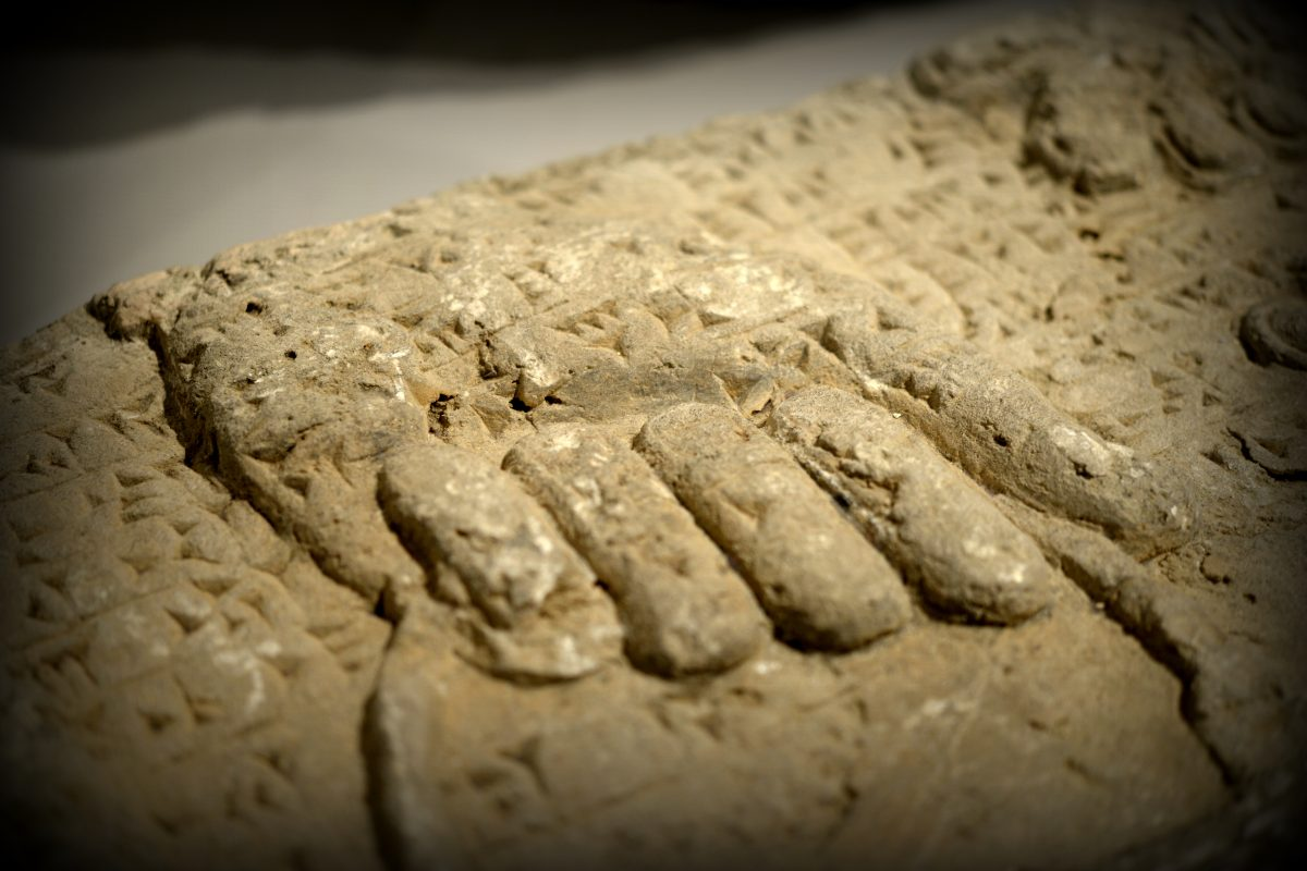 """Detail of a gypsum wall relief from the North-West at Nimrud. What has survived is a left hand of an Apkallu (Akkadian, which means sage). The hand grips on the handle of a buckle. The buckle is supposed to contain a fluid (?water for purification). The cuneiform text of the so-called """"Standard Inscription"""" of Ashurnasirpal II runs over the relief. At the right upper angle, part of the """"Sacred Tree"""" appears. Photo © Osama S. M. Amin."""