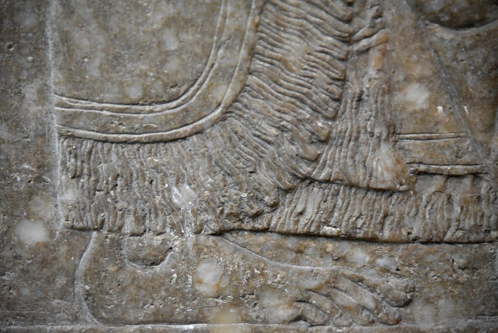 This detail of a large wall relief from Nimrud shows the lower part of the fringed wore by an eagle-headed protective spirit (Apkallu). His foot is bare. Compare this image with the similar image above, at the Sulaymaniyah Museum. The robe is different and this Apkallu stands between 2 sacred trees; there is no body before or behind him. From the North-West Palace at Nimrud, Room F, panel 8. Northern Mesopotamia, modern-day Iraq. Assyrian, 865-860 BCE. The British Museum, London. Photo © Osama S. M. Amin.