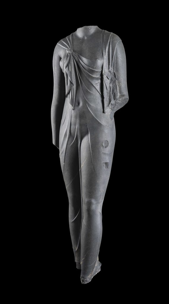 Cut in hard, dark stone, this feminine body has a startlingly sculptural quality. Complete, it must have been slightly larger than life-size. The statue is certainly one of the queens of the Ptolemaic dynasty (likely Arsinoe II) dressed as the goddess Isis, as confirmed by the knot that joins the ends of the shawl the woman wears, which was representative of the queens during this time period. The statue was found at the site of Canopus. ©Franck Goddio / Hilti Foundation - Photo: Christoph Gerigk. Sunken Cities exhibition.